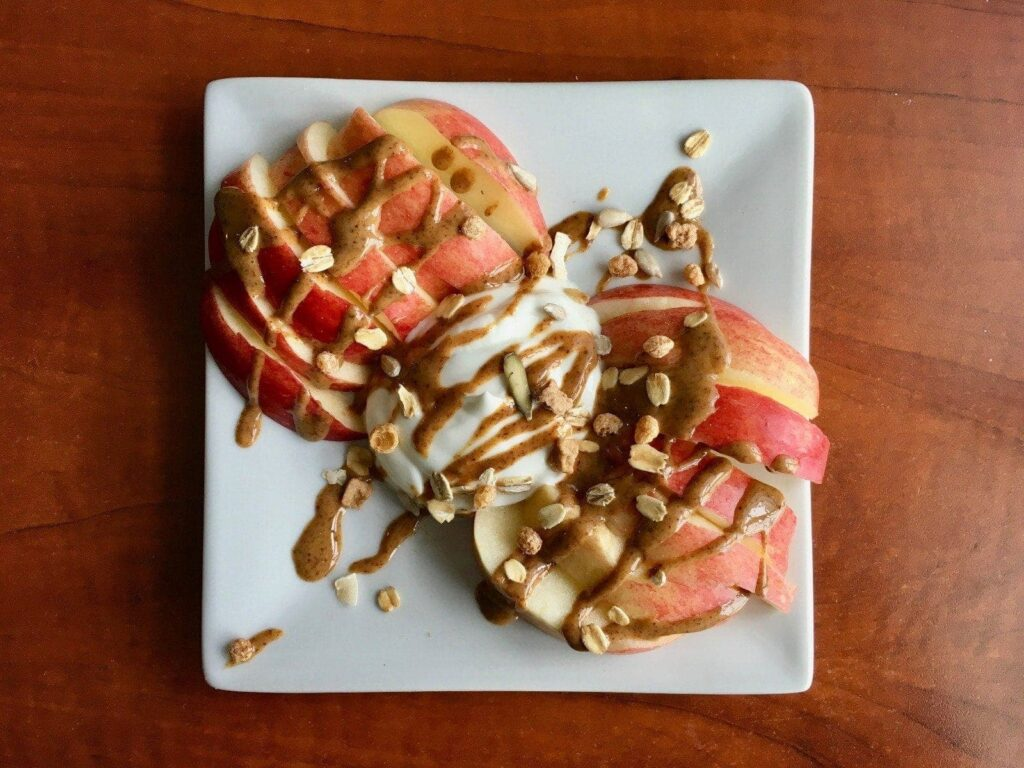 This is a picture of dressed-up apple slices. There are two rows of apple slices on a square plate with a scoop of yogurt in the middle of the plate. There is nut butter drizzled all over the apple slices along with granola sprinkled on top.