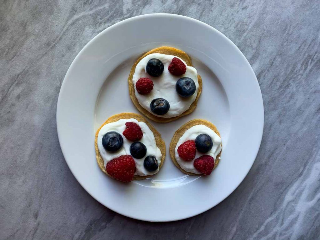 This is step two of Berries and Cream Mini Pancake Sliders. There are three pancakes topped with a layer of yogurt. On top of the yogurt there are blueberries and raspberries.