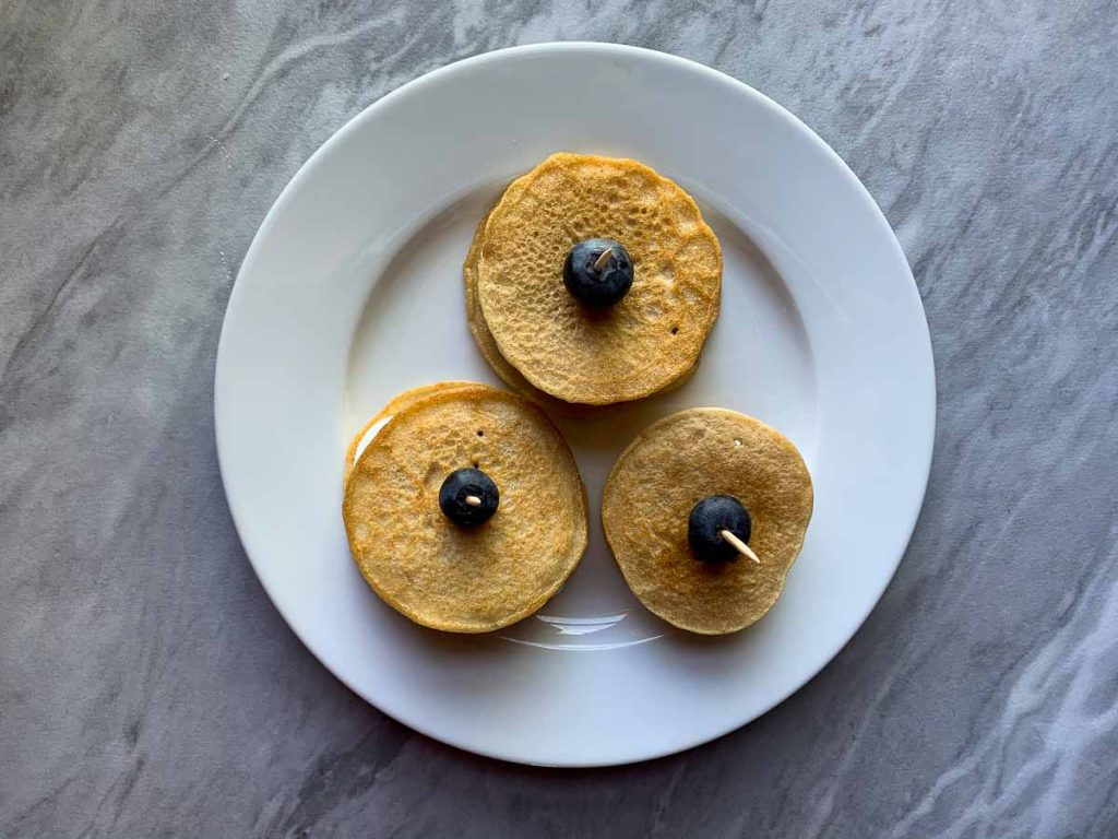 This is step 4 for Berries and Cream Mini Pancake Sliders. There are three stacks of pancakes with yogurt berries and pancakes on top and bottom. They are all held together by a toothpick with a blueberry on top.