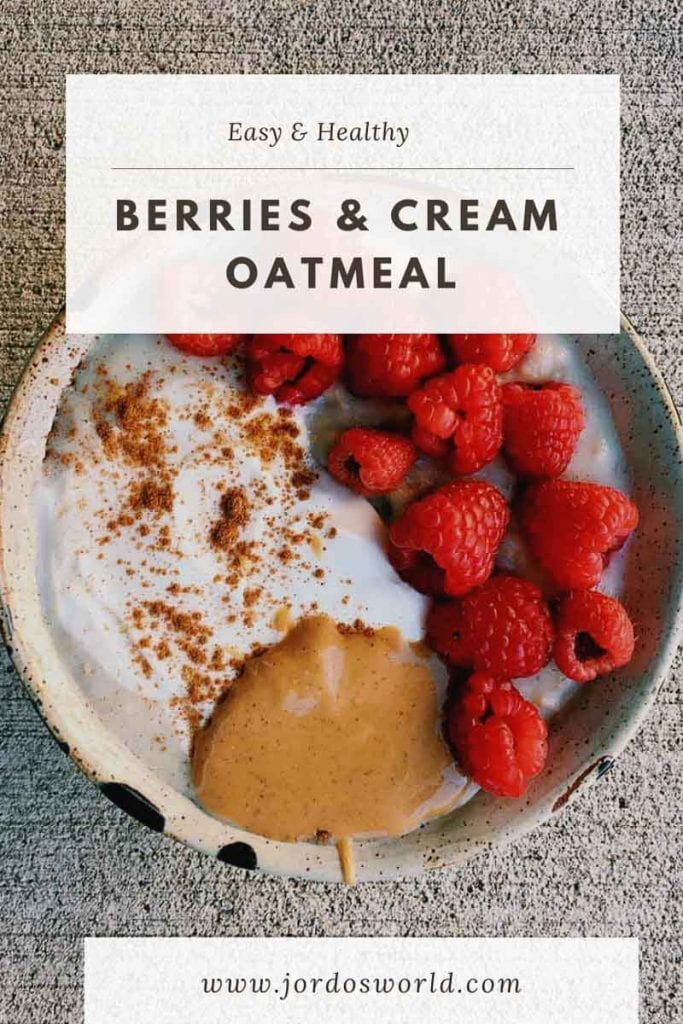 This is a pinterest pin for berries and cream protein oatmeal. There is a big tan ceramic bowl filled with oatmeal. The toppings are raspberries, nut butter, vanilla white yogurt, and sprinkled with cinnamon. The title of the recipe is at the top of the pin.