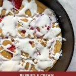 """This is a pinterest picture for the berries and cream pancake skillet. There is a black cast-iron skillet that is zoomed in so you can just see half of it. There is a light brown pancake inside of the skillet that is topped with red berries and a white cream sauce. The title of the recipe """"Berries and Cream Pancake Skillet"""" is on the bottom of the picture."""
