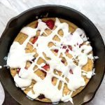 """This is a pinterest picture for the berries and cream pancake skillet. There is a black cast-iron skillet the pancake skillet is in. There is a light brown pancake inside of the skillet that is topped with red berries and a white cream sauce. The title of the recipe """"Berries and Cream Pancake Skillet"""" is on the top of the picture."""