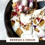 """This is a pinterest picture for the berries and cream pancake skillet. There is a black cast-iron skillet the pancake skillet is in. There is a light brown pancake inside of the skillet that is topped with red berries and a white cream sauce. There is a fork with a piece of pancake, berries, and cream on it zoomed in so you can see all the delicious details. The title of the recipe """"Berries and Cream Pancake Skillet"""" is on the top of the picture."""