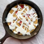 This berries and cream protein skillet is in a black cast-iron skillet on a marble slab. The pancake is light brown, and topped with raspberries, strawberries, and blueberries. There is white glaze drizzled all over the top as well.