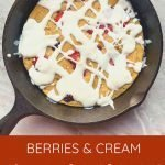 """This is a pinterest picture for the berries and cream pancake skillet. There is a black cast-iron skillet the pancake skillet is in. There is a light brown pancake inside of the skillet that is topped with red berries and a white cream sauce. The title of the recipe """"Berries and Cream Pancake Skillet"""" is on the bottom of the picture."""