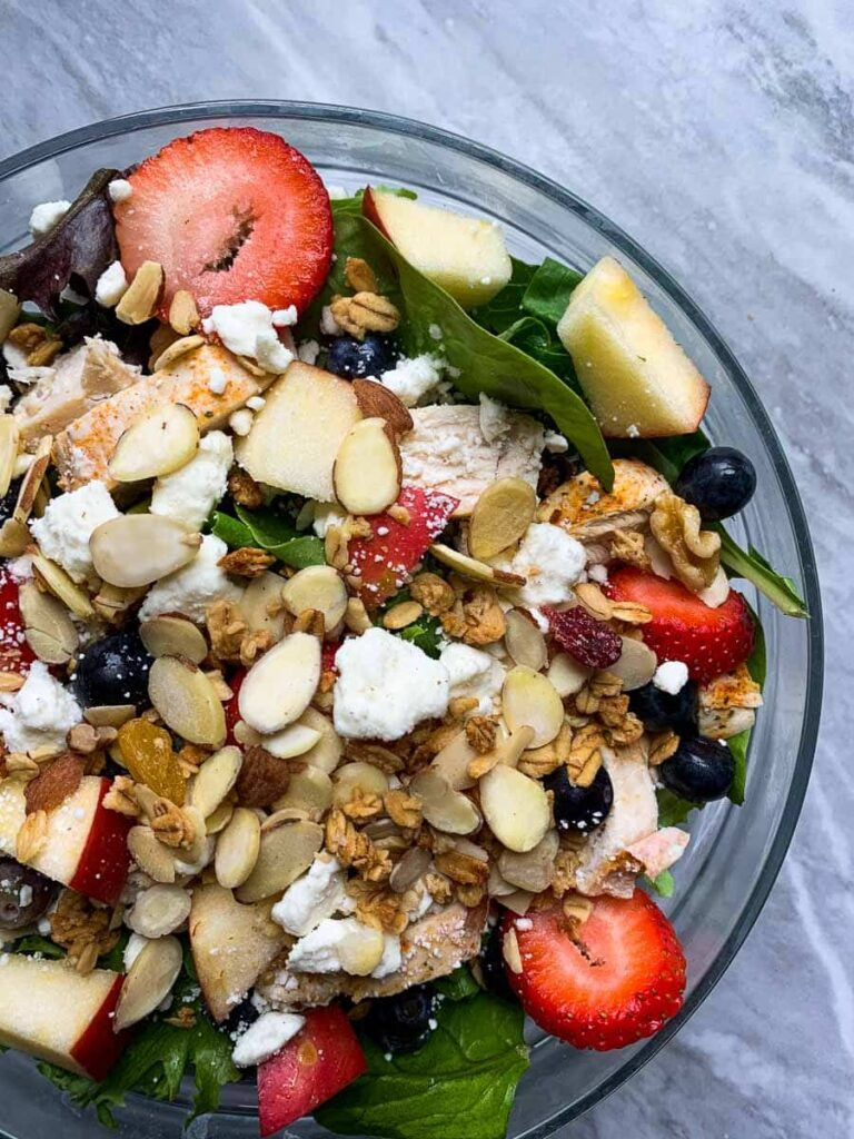 This is the copy cat chick-fil-a salad. There is a large glass bowl filled with mixed greens. It is topped with strawberries, blueberries, feta cheese, almonds, and granola.