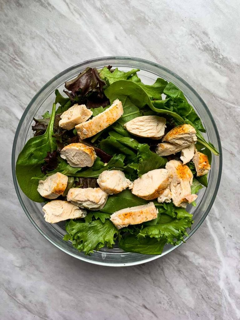 This is the first step to making the copy cat chick-fil-a salad. There is a large glass bowl filled with mixed greens and topped with slices of grilled chicken.