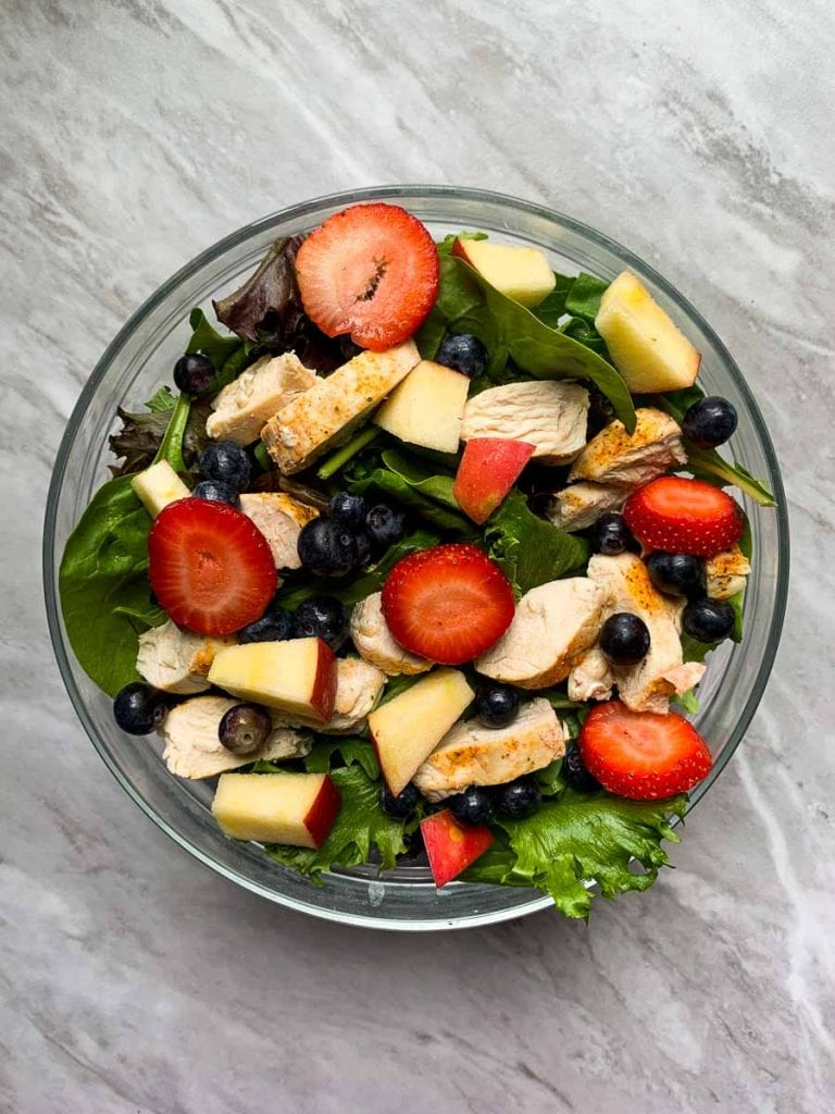 This is another step to the copy cat chick-fil-a salad. There is a large glass bowl filled with mixed greens. It is topped with strawberries, blueberries, apples, and chicken.