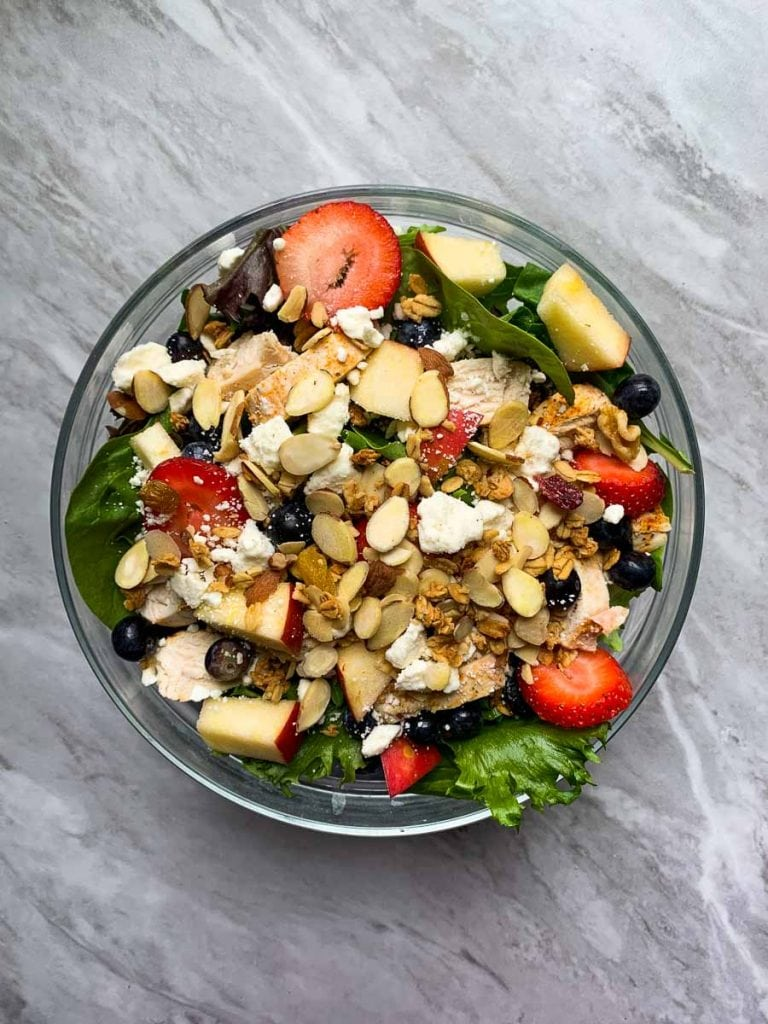 This is the copy cat chick-fil-a salad. There is a large glass bowl filled with mixed greens. It is topped with strawberries, blueberries, feta cheese, almonds, apples, and granola.