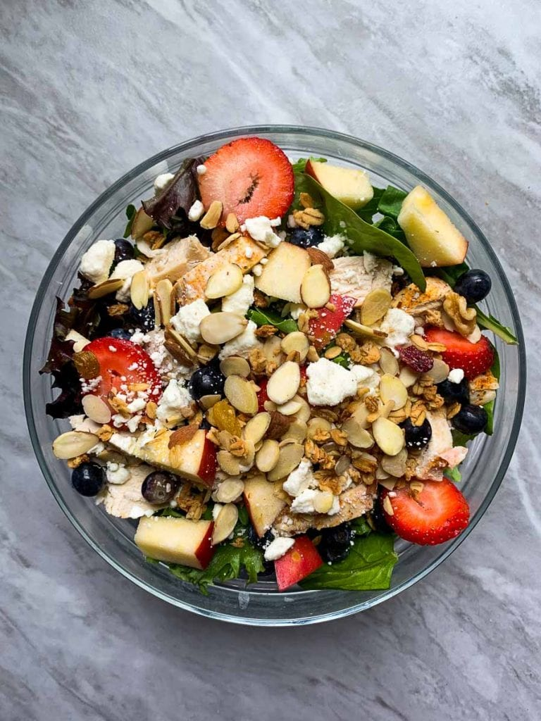 This is the copy cat chick-fil-a salad. There is a large glass bowl filled with mixed greens. It is topped with chicken, apples, strawberries, blueberries, feta cheese, almonds, and granola.