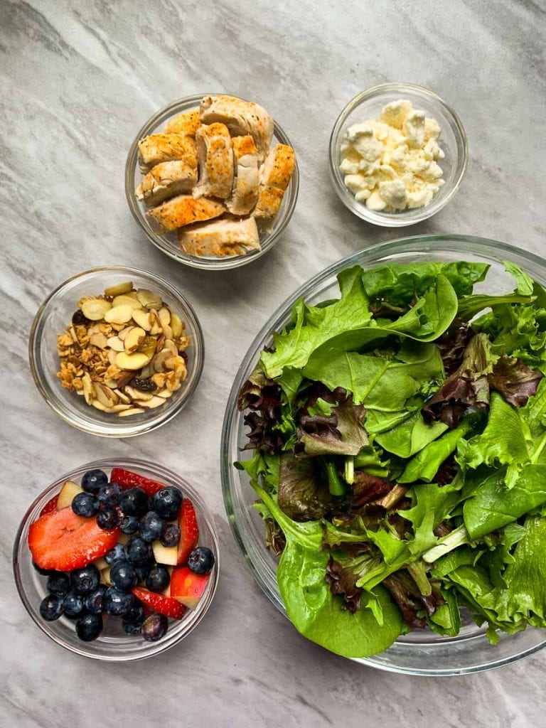 These are the ingredients for the copy cat chick-fil-a salad. There are glass bowls filled with mixed greens, strawberries and blueberries, feta cheese, almonds, chicken, and granola.