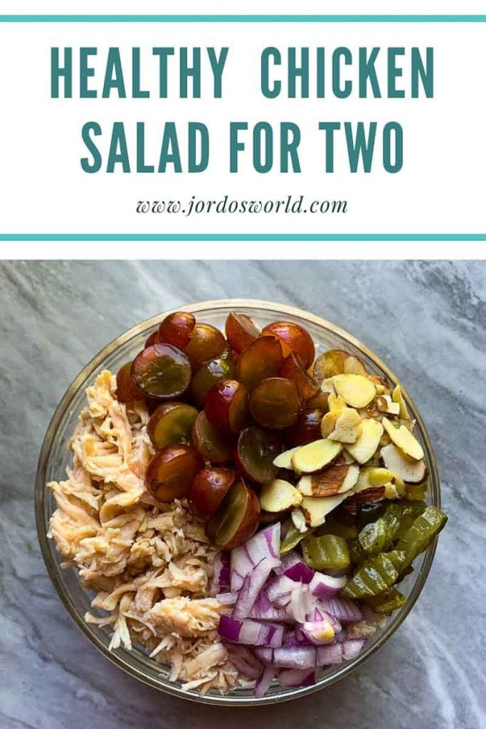 "This is a pinterest picture for a healthy chicken salad recipe. The image has a big glass bowl filled with all of the ingredients for the the healthy chicken salad. The chicken salad has chicken, grapes, almonds, red onions, and pickles all laid out in a circle in the bowl. The title of the recipe ""Healthy Chicken Salad for Two"" is on the top of the picture."