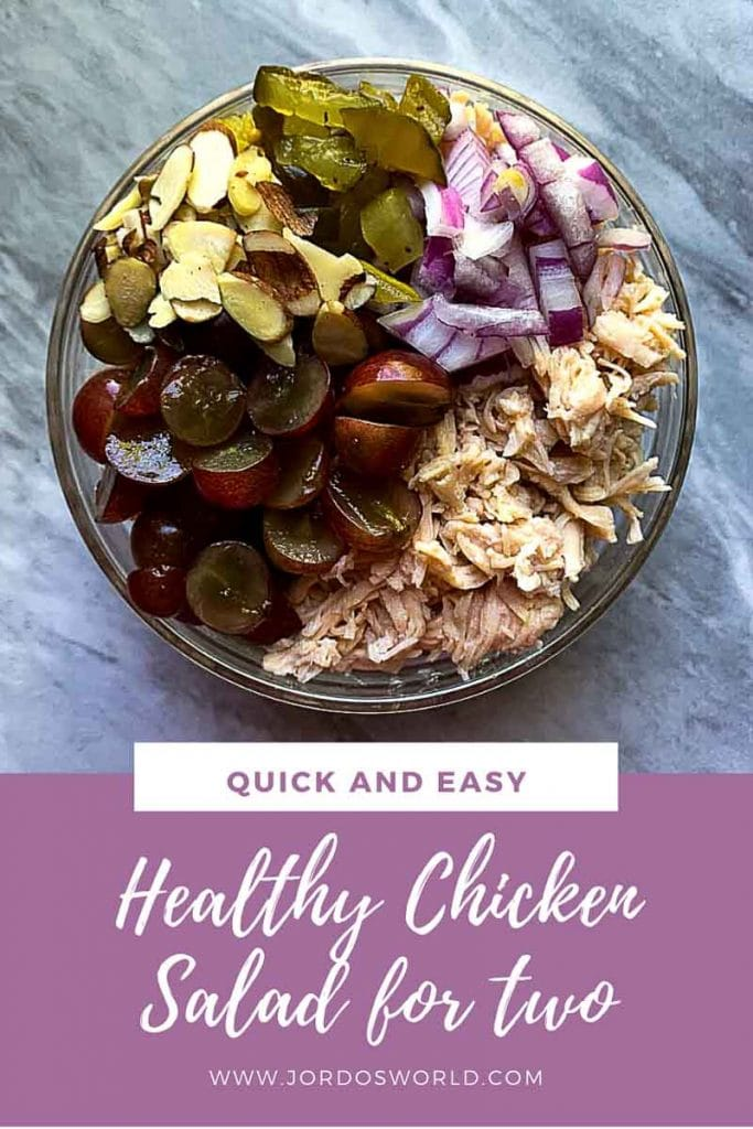 "This is a pinterest picture for a healthy chicken salad recipe. The image has a big glass bowl filled with all of the ingredients for the the healthy chicken salad. The chicken salad has chicken, grapes, almonds, red onions, and pickles all laid out in a circle in the bowl. The title of the recipe ""Healthy Chicken Salad for Two"" is on the bottom of the picture."