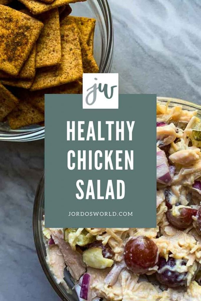 "This is a pinterest picture for a healthy chicken salad recipe. The image has a big glass bowl filled with the the healthy chicken salad. The chicken salad has chicken, grapes, almonds, red onions, and pickles all mixed together in a white sauce. There is also a bowl with wheat thins in the corner of the picture. The title of the recipe ""Healthy Chicken Salad"" is in the middle of the picture."