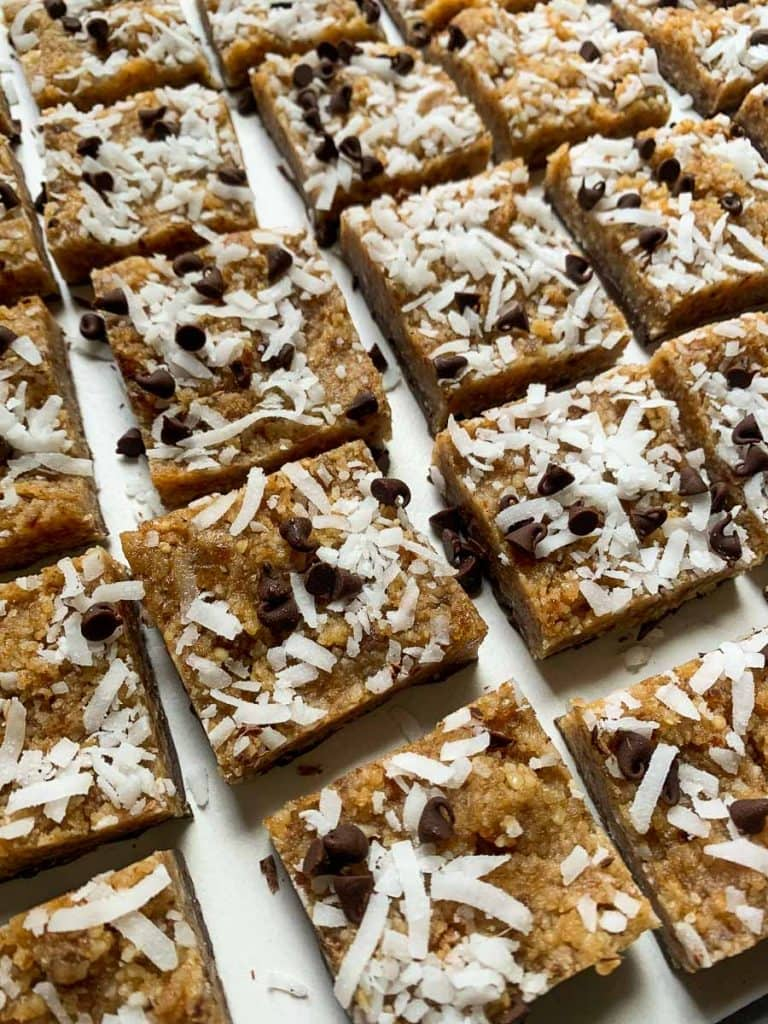 These coconut chocolate chip bars are lined in rows. They are healthy dessert bars topped with coconut and mini chocolate chips.