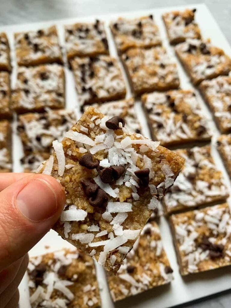 These coconut chocolate chip bars are lined in rows. They are healthy dessert bars topped with coconut and mini chocolate chips. There is a hand holding up a piece of the bar close to the camera so you can see the thickness, details, and layer of chocolate.