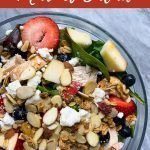 """This is a pinterest image for the copy cat chick-fil-a market salad. There is a large glass bowl filled with the market salad. The bowl has mixed greens topped with grilled chicken, mixed berries, apples, feta cheese, almonds and granola. The title of the recipe, """"Copy Cat Chick-Fil-A Market Salad"""" is on top of the pinterest image."""
