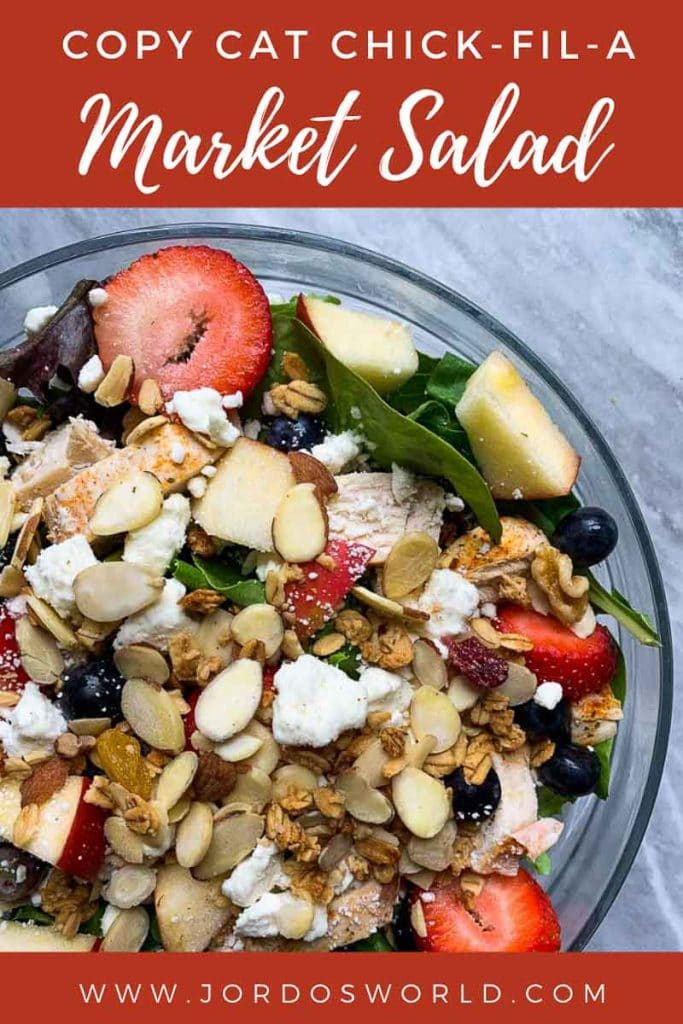 "This is a pinterest image for the copy cat chick-fil-a market salad. There is a large glass bowl filled with the market salad. The bowl has mixed greens topped with grilled chicken, mixed berries, apples, feta cheese, almonds and granola. The title of the recipe, ""Copy Cat Chick-Fil-A Market Salad"" is on top of the pinterest image."