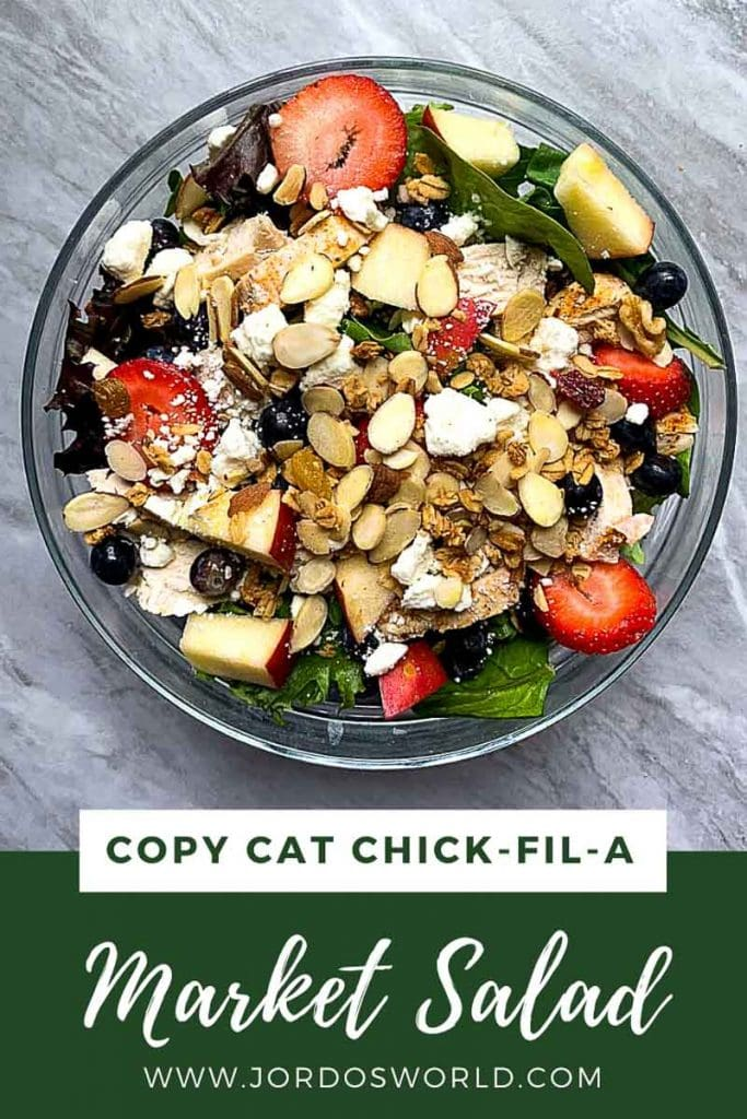 "This is a pinterest image for the copy cat chick-fil-a market salad. There is a large glass bowl filled with the market salad. The bowl has mixed greens topped with grilled chicken, mixed berries, apples, feta cheese, almonds and granola. The title of the recipe, ""Copy Cat Chick-Fil-A Market Salad"" is on the bottom of the pinterest image."