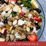 """This is a pinterest image for the copy cat chick-fil-a market salad. There is a large glass bowl filled with the market salad. The bowl has mixed greens topped with grilled chicken, mixed berries, apples, feta cheese, almonds and granola. The title of the recipe, """"Copy Cat Chick-Fil-A Market Salad"""" is on the bottom of the pinterest image."""