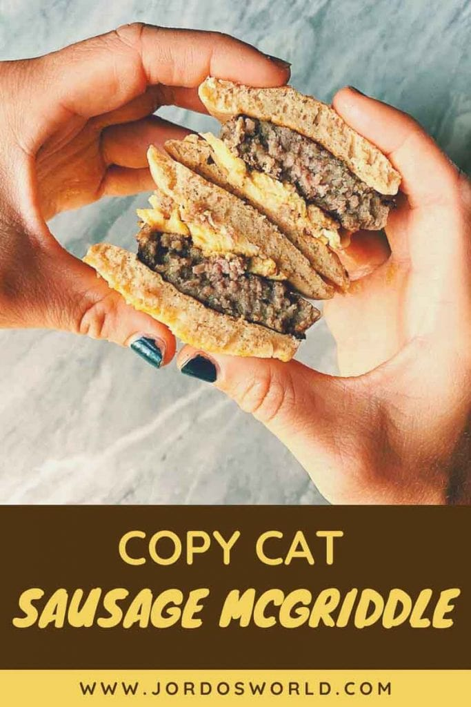 This is a pinterest picture for the copy cat sausage mcgriddle recipe. There is a pair of hands holding a sausage mcgriddle with a marbled background. The mcgriddles are sandwiches made with pancakes, sausages, and eggs. The picture has the sandwich cut in half so you can see all the layers.