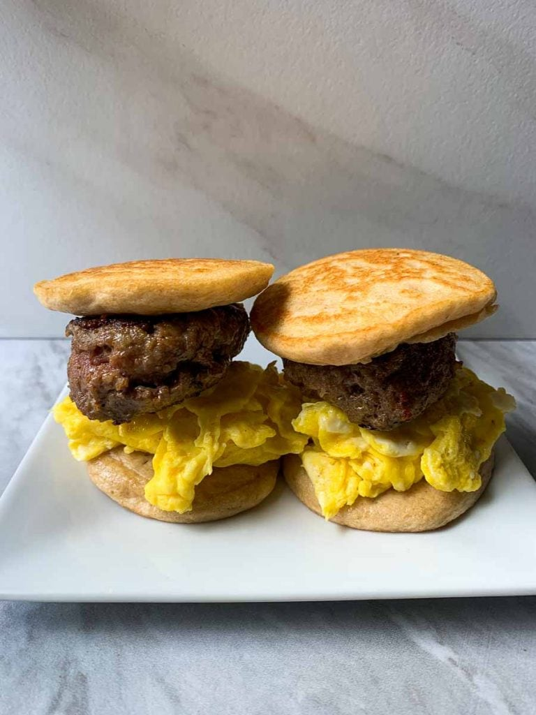 These are copy cat sausage mcgriddles. There are pancake sandwiches with a sausage patty and eggs in the middle. This picture has a small white plate with two mcgriddles.