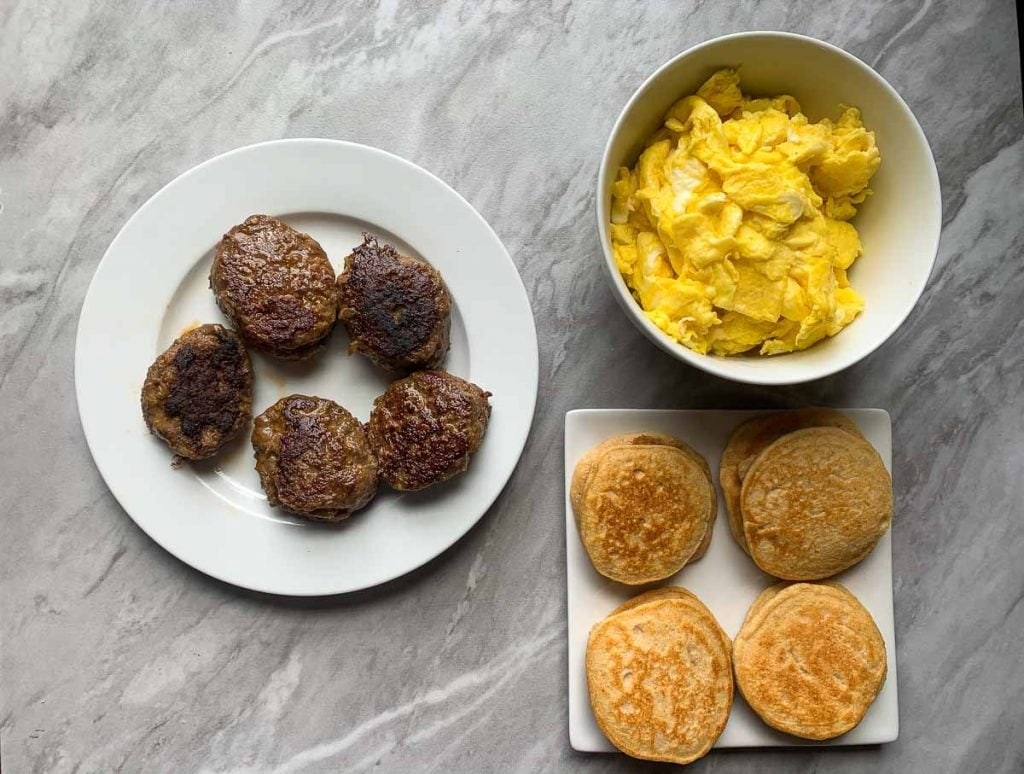 These are the cooked ingredients for the recipe. There is a plate of cooked sausage patties, a bowl of eggs, and cooked mini pancakes. These ingredients will be assembled into the mcgriddles.
