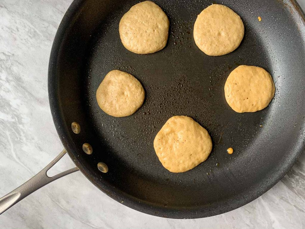 This is a large skillet with pancakes cooking on it. There are five pancakes, each about 3 inches that are cooking.