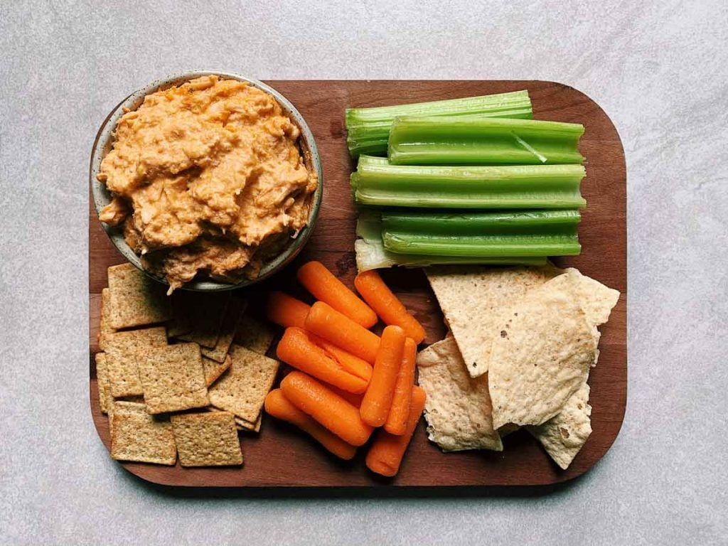 This is healthier buffalo chicken is in a bowl and it is on a platter with a bunch of things to dip. The things around the bowl like celery, carrots, tortilla chips and crackers.