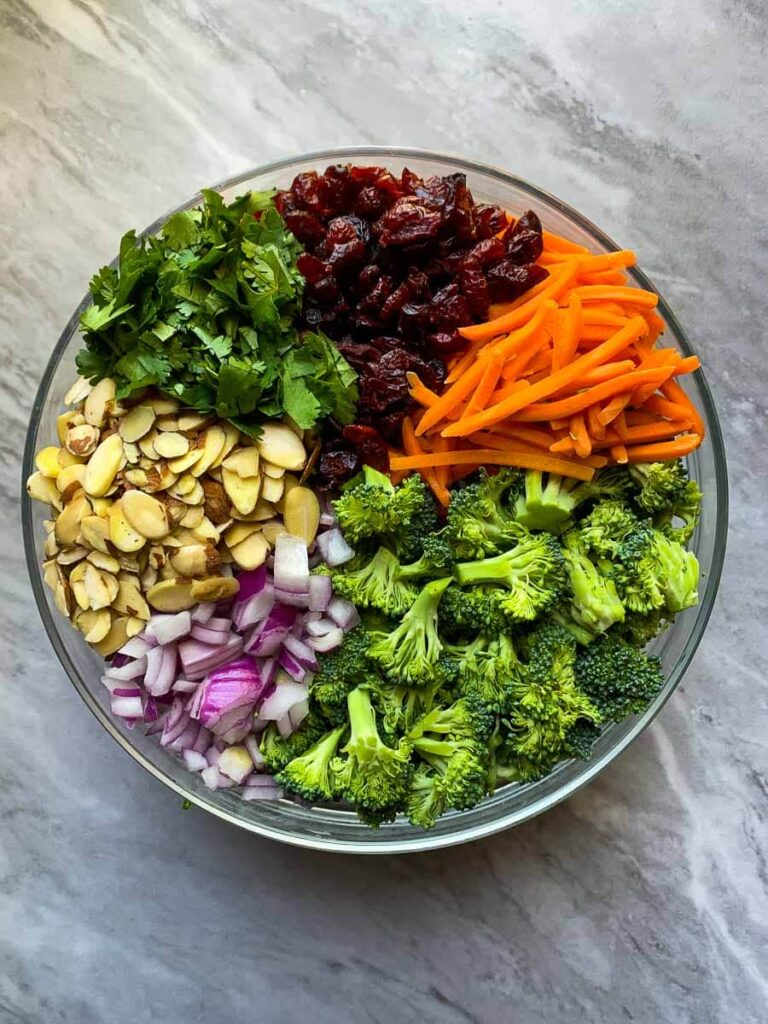 This is a bowl filled with ingredients for a healthy summer broccoli salad. The ingredients are rotated in a circle. There is diced red onion, slivered almonds, diced cilantro, dried cranberries, chopped carrot, and chopped broccoli.