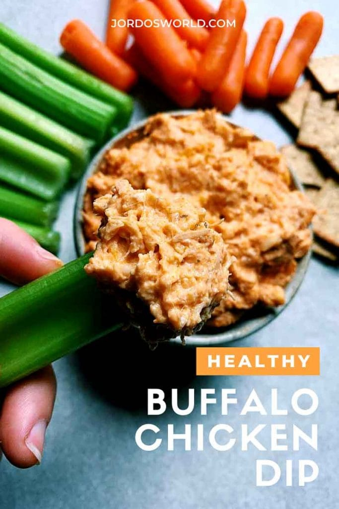 This is a pinterest picture for a healthier buffalo chicken dip recipe. There is a small green circle ceramic bowl filled with buffalo chicken dip. The dip is a light orange shredded chicken and cheese dip. There is a hand holding a piece of green celery with buffalo chicken dip on the end. There are also pieces of celery, carrots, and wheat thins for around the bowl to be used for dipping.