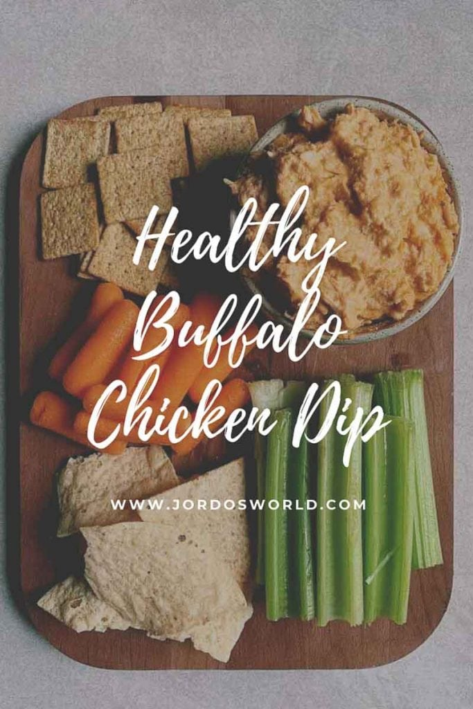 This is a pinterest picture for a healthier buffalo chicken dip recipe. There is a small green circle ceramic bowl filled with buffalo chicken dip. The dip is a light orange shredded chicken and cheese dip. There are also pieces of celery, carrots, and wheat thins on a brown platter around the bowl to be used for dipping.