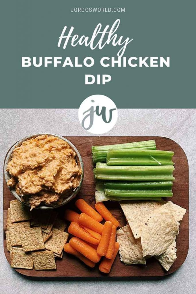 This is a pinterest picture for a healthier buffalo chicken dip recipe. There is a small green circle ceramic bowl filled with buffalo chicken dip. The dip is a light orange shredded chicken and cheese dip. There are also pieces of celery, carrots, and wheat thins on a brown cutting board next to the bowl of dip to be used for dipping.
