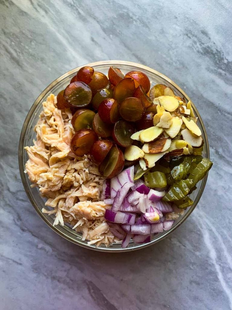 This is the healthy chicken salad. Everything is in a bowl with all of the ingredients in sections. There is a section with grapes, almonds, pickles, red onions, shredded chicken.