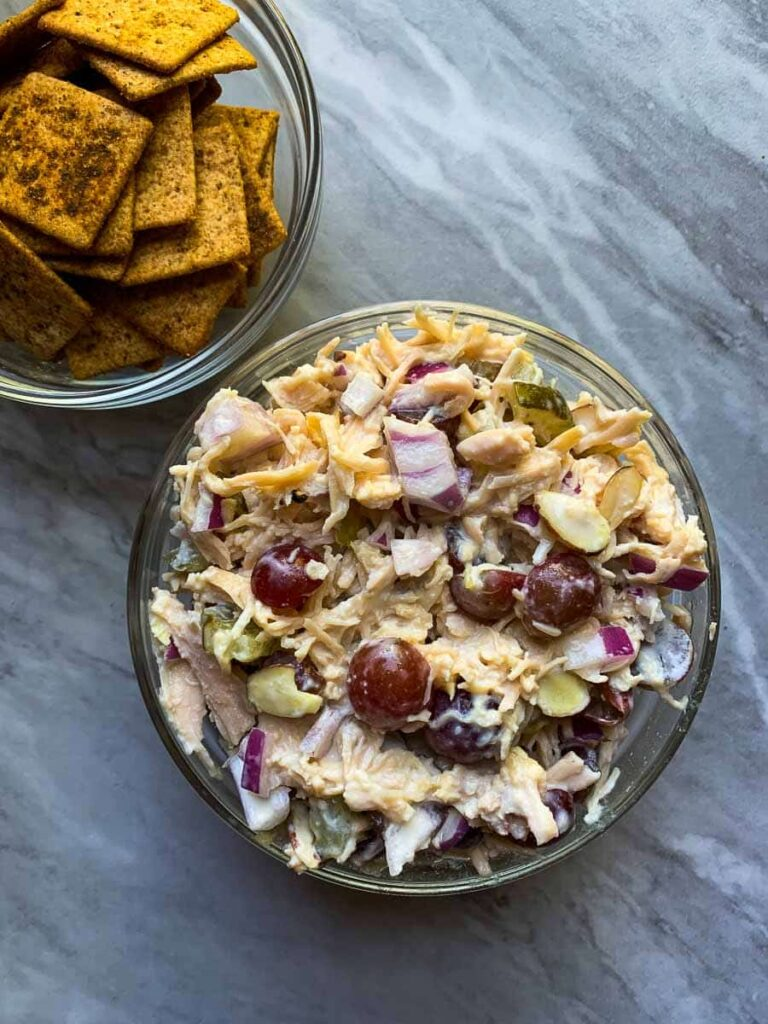 There is a medium-size clear bowl filled with healthy chicken salad. The chicken salad has shredded chicken, grapes, red onion, and pickles. There is also a small bowl of brown wheat thin crackers.