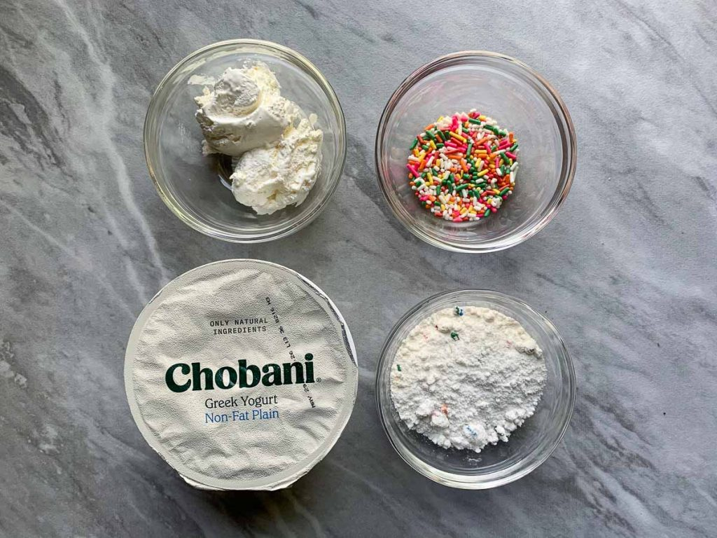 These are the ingredients for healthy funfetti cake batter dip. There are four ingredients placed on a marble backdrop. There is a small bowl of whipped cream, a small bowl of sprinkles, and a small bowl of funfett cake mix. There is also a small container of Chobani plain greek yogurt.