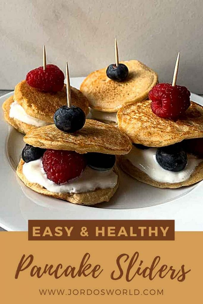 """This is a pinterest picture for the berries and cream pancake sliders recipe. There is a small white plate that has four pancake sliders. The pancake sliders are pancake sandwiches made up of a layer of pancake, vanilla greek yogurt, and berries topped with another pancake. These are held together with a toothpick and a berry on top of that. The bottom of the picture has the title of the recipe, """"Easy and Healthy Pancake Sliders""""."""