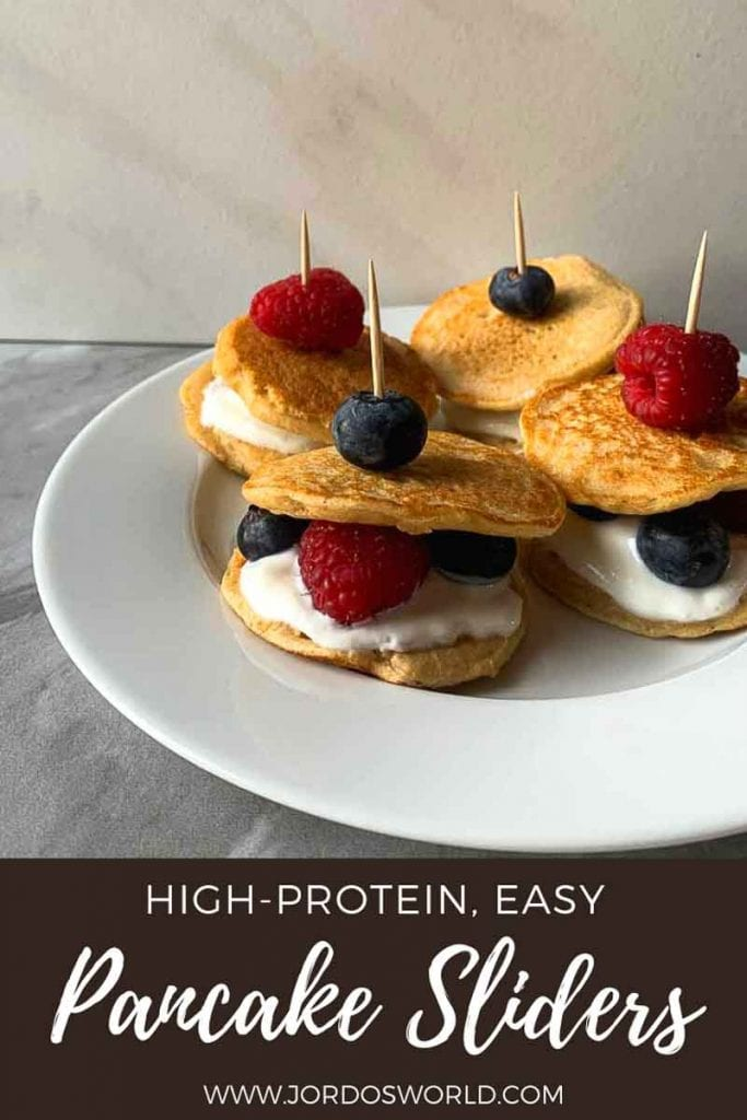 """This is a pinterest picture for the berries and cream pancake sliders recipe. There is a small white plate that has four pancake sliders. The pancake sliders are pancake sandwiches made up of a layer of pancake, vanilla greek yogurt, and berries topped with another pancake. These are held together with a toothpick and a berry on top of that. The bottom of the picture has the title of the recipe, """"High-Protein, Easy Pancake Sliders""""."""
