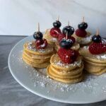 This is a plate of patriotic pancake pops. There are stacks of mini pancakes with a raspberry and blueberry on top, all held together with a skewer. They all have powdered sugar sprinkled on top.