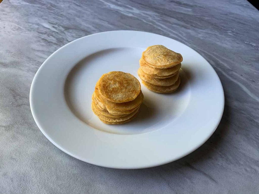 This is a picture of two small stacks of pancakes on a plate. Each stack has about 7 mini pancakes.