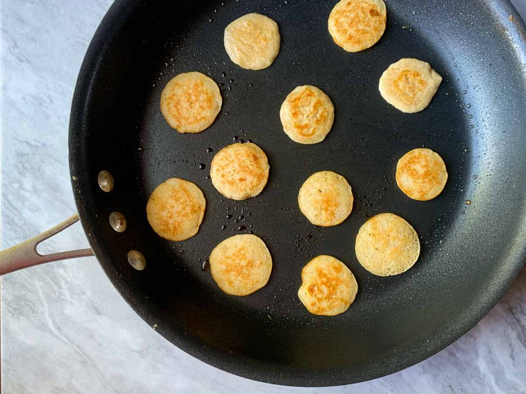 This is a picture of a skillet filled with small, lightly-browned mini pancakes.