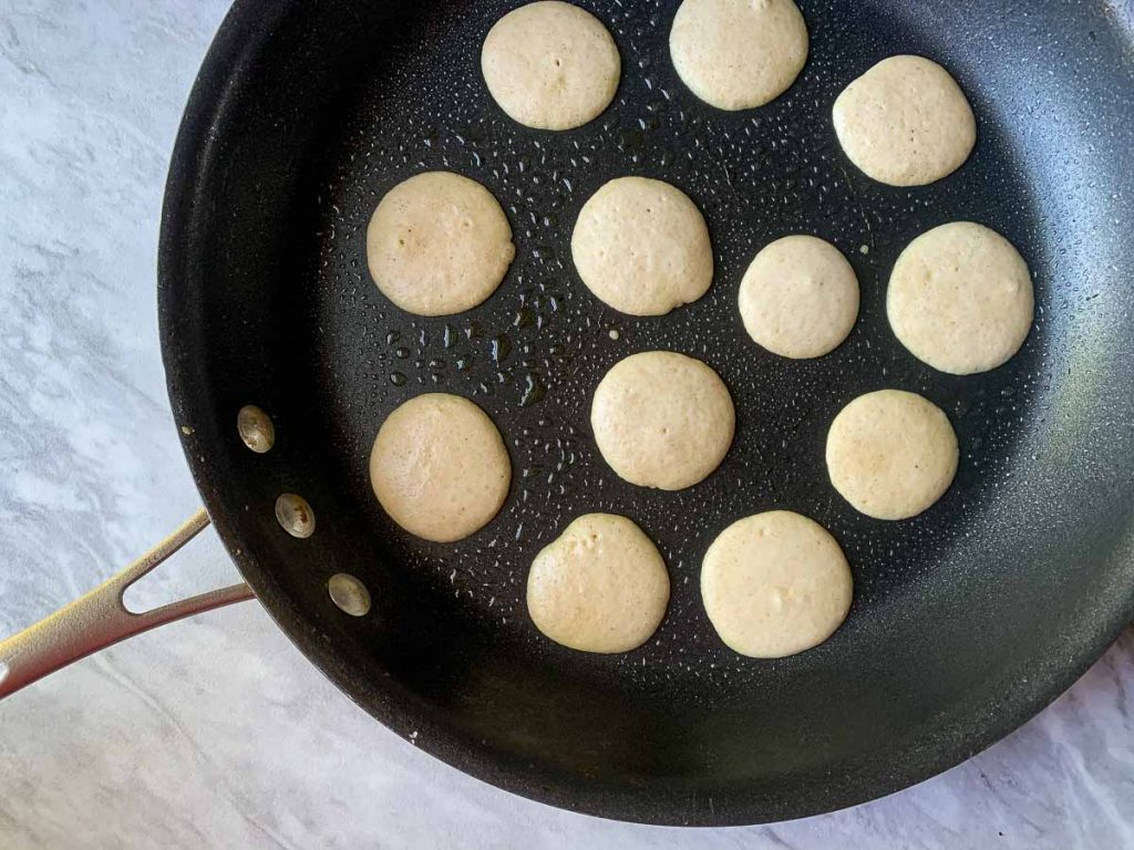 This is a picture of a skillet filled with small mini pancakes. The pancakes are still batter as they are not cooked completely yet.