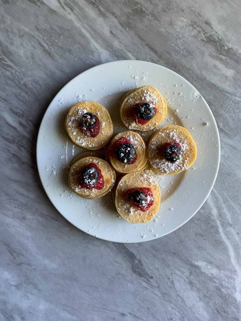 This is a top-down view of a plate of patriotic pancake pops. There are six stacks of mini pancakes with a raspberry and blueberry on top, all held together with a skewer. They all have powdered sugar sprinkled on top.