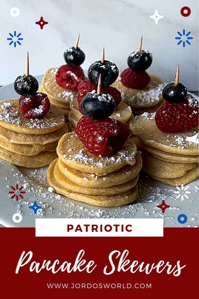 """This is a pinterest picture for patriotic pancake skewers. There is a small circle white plate that has 5 pancake skewers. Each skewer has four mini protein pancakes topped with a raspberry and blueberry held together with a toothpick. Each skewer is sprinkled with powdered sugar. The title of the recipe, """"Patriotic Pancake Skewers"""" is also on the image."""