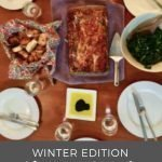 "Pinterest image of a set table for a dinner party feature an entree of lasagna, kale salad, and bread. Oil and balsamic vinegar dip. Superimposed text reads ""winter edition dinner party."""