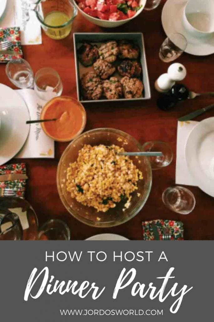 "This is a pin for how to host a dinner party. There is a picture of a table set with nice plates, cups, napkins, and utensils with food. There are also bowls of watermelon arugula salad and mexican street corn on the table. The title of the post, ""How to Host a Dinner Party"" is across the image."
