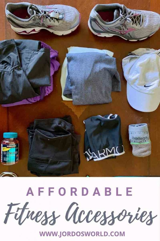 """This is a pin for my affordable fitness accessories post. There is a table with a water bottle, clothes, and snacks. The title of the post, """"Affordable Fitness Accessories"""" is across the bottom of the post."""