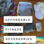 "This is a pin for my affordable fitness accessories post. There is a table with a water bottle, clothes, and snacks. The title of the post, ""Affordable Fitness Accessories"" is across the post."