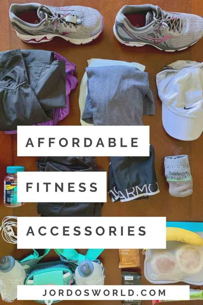 """This is a pin for my affordable fitness accessories post. There is a table with a water bottle, clothes, and snacks. The title of the post, """"Affordable Fitness Accessories"""" is across the post."""