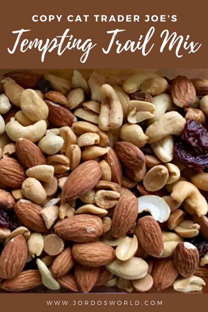 This is a pin for the Copy Cat Trader Joe's Tempting Trail Mix recipe. There is a picture of trail mix with nuts, dried fruit and chocolate. The title of the post, Tempting Trail Mix, is at the top of the post.